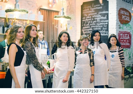 KYIV, UKRAINE - December 13, 2014: Happy group of friends with male chef cook cooking and talking in kitchen. Cooking class. - stock photo