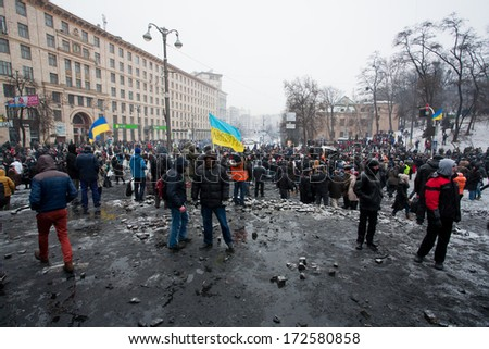 KYIV, UKRAINE - JAN 21: Crazy crowd of protesters walking in the burned square after fight with police in capital during anti-government revolution Euromaidan on January 21, 2014, in Kiev, Ukraine.   - stock photo
