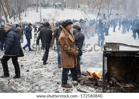KYIV, UKRAINE - JAN 21: Elderly man in coat burn fire near the barricades on the snowing street during two months anti-government protest Euromaidan on January 21, 2014, in Kiev, Ukraine.   - stock photo
