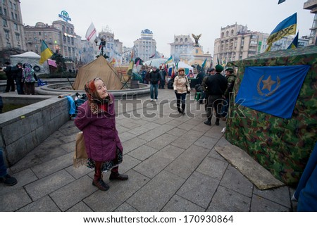 KYIV, UKRAINE - JAN 7: Elderly woman looks at the camp protesters anti-government revolution on January 7, 2013. Population of 2,847,200 people making Kiev at least 8-th largest city in Europe. - stock photo