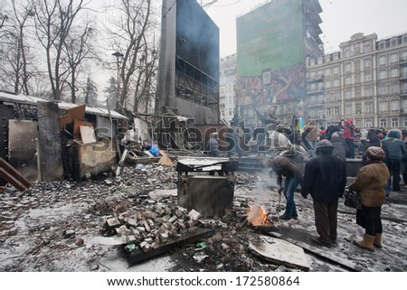 KYIV, UKRAINE - JAN 21: People heating by the fire near the barricades after fights with police on the broken pavement street during anti-government protest on January 21, 2014, in Kiev, Ukraine.   - stock photo