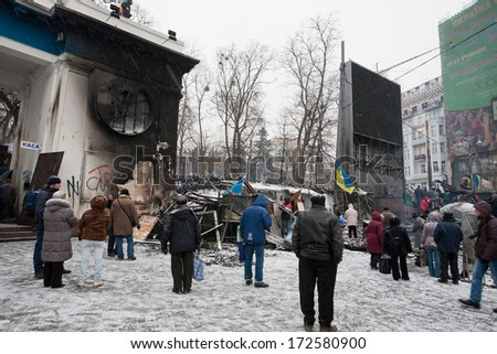 KYIV, UKRAINE - JAN 21: People stand near the barricades hide police squads behind on the occupying snow street during anti-government protest Euromaidan on January 21, 2014, in Kiev, Ukraine.  - stock photo