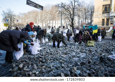 KYIV, UKRAINE - JAN 23: Peoples picking stones on Hrushevskogo street during anti-government protest Euromaidan on January 23, 2014, in center of Kiev, Ukraine