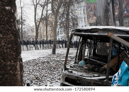 KYIV, UKRAINE - JAN 21: Police squads stand behind the burned buses and barricades waiting for the order to attackon during anti-government protest Euromaidan on January 21, 2014, in Kiev, Ukraine - stock photo
