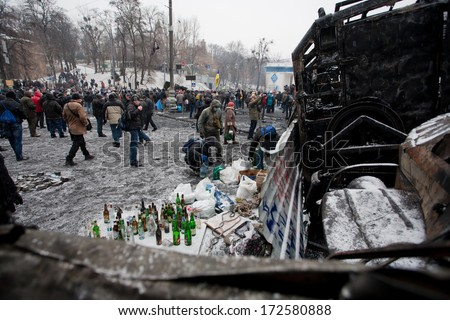KYIV, UKRAINE - JAN 21: Protesters prepare Molotov cocktail with gasoline on the barricades and wait for fights with police during anti-government protest on January 21, 2014, in Kiev, Ukraine.   - stock photo