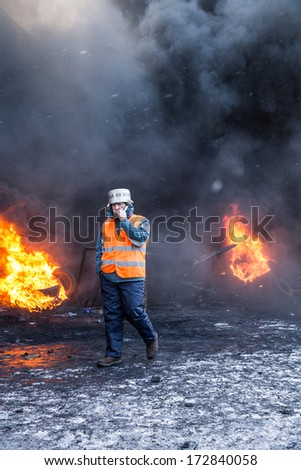 KYIV, UKRAINE - JAN 23: Smoking man on the occupying street on the demostration during anti-government protest Euromaidan on January 23, 2014, in center of Kiev, Ukraine - stock photo