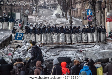 Kyiv, Ukraine - January 24, 2014 Lanes of riot police facing protesters during mass protests on Grushevskogo Str. - stock photo