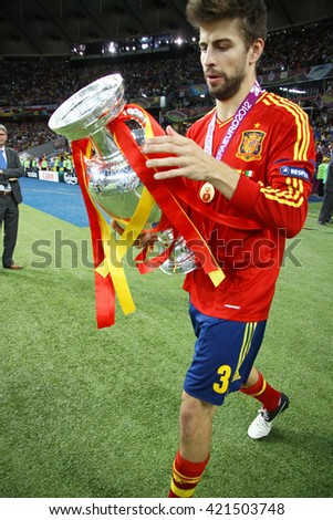 KYIV, UKRAINE - JULY 1, 2012: Gerard Pique of Spain walks on with Trophy after UEFA EURO 2012 Final game against Italy at Olympic stadium in Kyiv. Spain won the game and the Tournament - stock photo