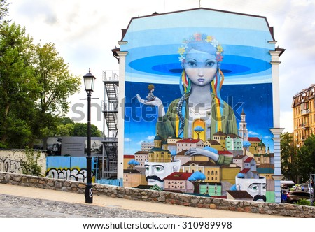 """KYIV, UKRAINE - JULY 7th, 2015 : Beautiful graffiti painting entitled """"Revival"""" at Andriyivskyy Descent, so called Montmartre of Kyiv. Painting represents Ukraine as a girl in the national closing.  - stock photo"""