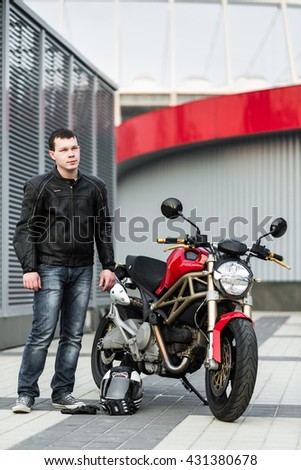 Kyiv, Ukraine - July 7th, 2015: The young man near red motorcycle Ducati Monster at the city street.