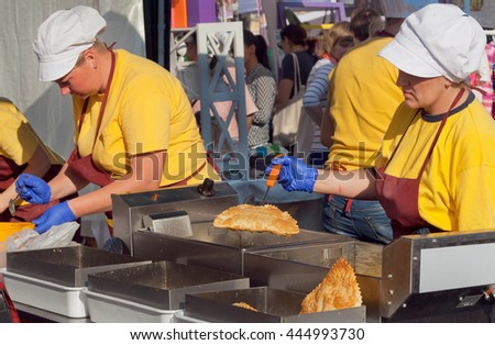 KYIV, UKRAINE - JUN 4: Women on kitchen of restaurant cooking fried food like the stuffed pies during a street festival on June 4, 2016. Kiev is the 8th most populous city in Europe.