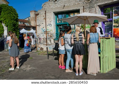 KYIV, UKRAINE - JUNE 6, 2015: Outdoor bar on the old street and young girls buying drinks during the Kiev Food & Wine Festival on June 20, 2014. Ukrainian capital, Kiev has population near 2,900,200  - stock photo