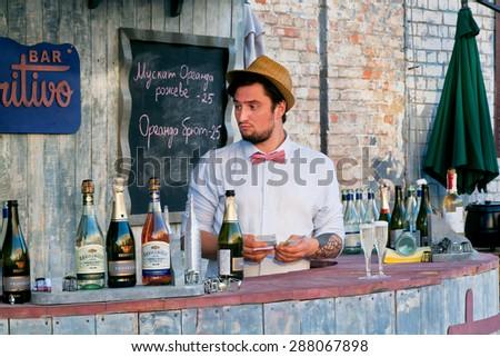KYIV, UKRAINE - JUNE 8, 2015: Young bartender count money revenue for drinks behind the bar table in outdoor restaurant on June 8, 2015. Ukrainian capital, Kiev has population near 2,900,200 people - stock photo