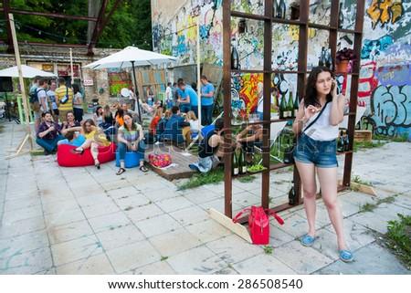 KYIV, UKRAINE - JUNE 6, 2015: Young girl calling phone in crowd of outddor bar during the Kiev Food & Wine Festival on June 6, 2015. Ukrainian capital, Kiev has population near 2,900,200   - stock photo