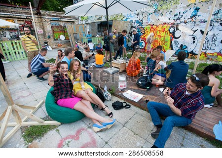 KYIV, UKRAINE - JUNE 6, 2015: Young people drinks cocktails at outdoor bar during the Kiev Food & Wine Festival on June 6, 2015. Ukrainian capital, Kiev has population near 2,900,200  - stock photo