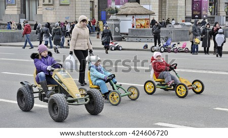 KYIV, UKRAINE - MARCH 17, 2013: Folk celebrating the Shrovetide on Kreschatik street. Three Children on childish cars.