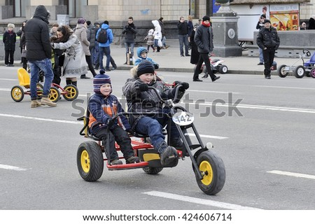 KYIV, UKRAINE - MARCH 17, 2013: Folk celebrating the Shrovetide on Kreschatik street. Two boys on two-place childish bicycles