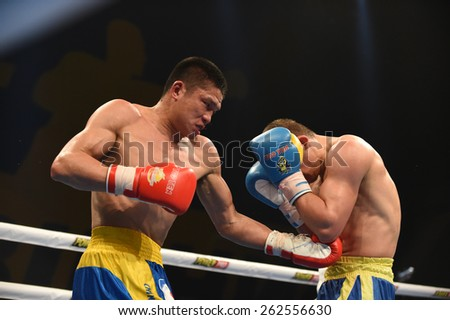 Kyiv, UKRAINE - March 20, 2015 : KHYZHNIAK Oleksandr (UA) and WANG ZHIBAO (China) in the ring during boxing fight Ukraine Otamans vs China Dragons in Palace of Sport in Kiev, Ukraine