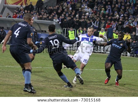 KYIV, UKRAINE - MARCH 10: Oleg Gusev of Dynamo Kyiv (in white) fights for a ball with Manchester City players during their UEFA Europa League game on March 10, 2011 in Kyiv, Ukraine