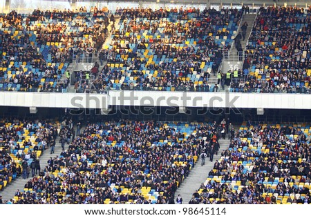 KYIV, UKRAINE - MARCH 18: People watch the football game of Ukraine Championship between FC Dynamo Kyiv and FC Dnipro at NSC Olimpiyskiy stadium on March 18, 2012 in Kyiv, Ukraine