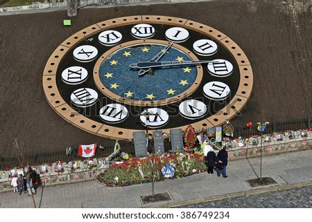 KYIV, UKRAINE - MARCH 06, 2016: Three memorials near earth clock, flowers and peoples. Second anniversary of perish of  the Heroes of Sky Hundred in events of Euromaydan