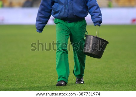 KYIV, UKRAINE - MARCH 5, 2016:  Ukrainian Football Premier League game. Dynamo Kyiv against Dnipro Dnipropetrovsk. Man without hands carries a bucket