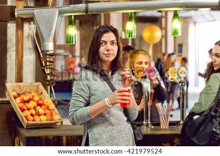 KYIV, UKRAINE - MAY 15: Young happy woman buying glass of tasty cider at bar of popular Street Food Festival on May 15, 2016. Kiev is the 8th most populous city in Europe. - stock photo