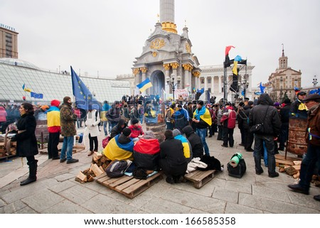 KYIV, UKRAINE - NOV 28: Many students sitting by the barrel with fire on the cold occupying street during two weeks of anti-government protest on November 28, 2013, in Kiev, Ukraine. - stock photo