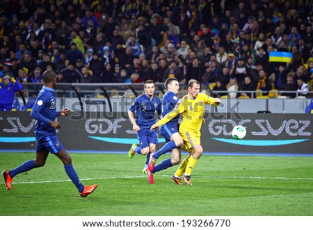 KYIV, UKRAINE - NOVEMBER 15, 2013: Roman Zozulya of Ukraine (in Yellow) attacks during FIFA World Cup 2014 play-off game against France - stock photo