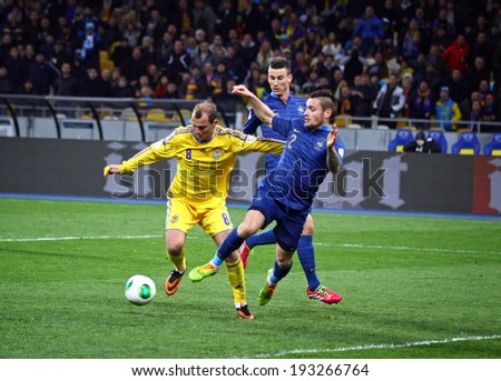 KYIV, UKRAINE - NOVEMBER 15, 2013: Roman Zozulya of Ukraine (in Yellow) fights for a ball with Mathieu Debuchy of France during their FIFA World Cup 2014 play-off game at NSC Olympic stadium - stock photo