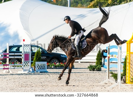 KYIV, UKRAINE - OCTOBER 10, 2015: A participant of competitions in jumping demonstration overcomes obstacle during international equestrian tournament - stock photo