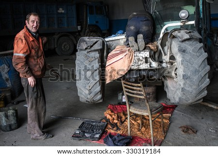 KYIV, UKRAINE-October 10, 2015, City garbage dump. Technician repairing a tractor that runs on landfill