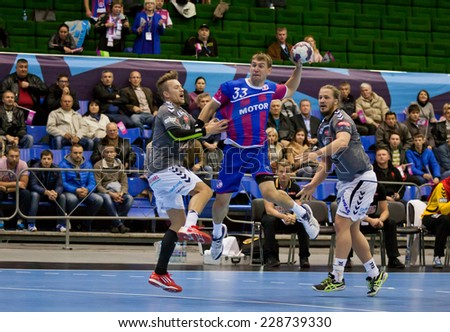 KYIV, UKRAINE - OCTOBER 18, 2014: Sergiy Onufrienko of Motor (C) attacks during European Handball Champions League game against Aalborg - stock photo