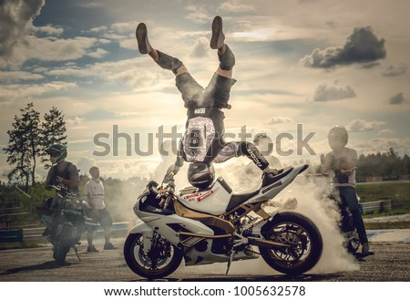 Kyiv / Ukraine - 07 15 2017: Stunt show!  The stuntman burns the tire, standing upside down on his head on the motocycler's tank at sunset.Tricks on sportbikes. Stunts on sportbikes. Burns the tire.