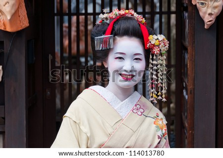 KYOTO - APRIL 10 2012: A Geisha poses for a photo in Gion district in Kyoto on April 10 2012. Geisha is traditional Japanese female entertainer. They can be spotted mostly in Gion district in Kyoto. - stock photo