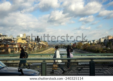 KYOTO, JAPAN - DECEMBER 03, 2014: Pedestrians cross the bridge walking towards Kyoto, Japan on the way to work on a winter morning. Kyoto is the old capital of Japan and still a thriving city today. - stock photo