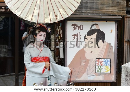 KYOTO, JAPAN - JULY 2: Maiko posing with Japanese poster. Apprentice geisha in Japan. Their jobs consist of performing songs, dances, and playing the shamisen. Kyoto, Japan - July 2, 2015 - stock photo