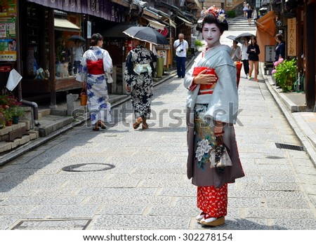 KYOTO, JAPAN - JULY 2: Maiko walking in Kyoto street. Apprentice geisha in Japan. Their jobs consist of performing songs, dances, and playing the shamisen. Kyoto, Japan - July 2, 2015 - stock photo