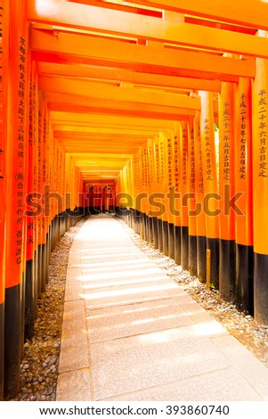 KYOTO, JAPAN - JUNE 15, 2015: Japanese text written on colorful red torii gates supports repeating at Fushimi Inari Taisha Shrine with no people present. Vertical copy space - stock photo