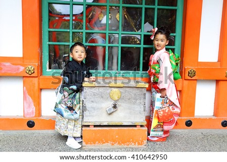 KYOTO, JAPAN - Nov 3: Boy and Girl stand at Fushimi Inari taisha shrine on November 3, 2015 in Kyoto, Japan. Including trails up the mountain to many smaller shrines which span 4 kilometers  - stock photo
