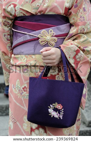 KYOTO, JAPAN - NOVEMBER 4: Geisha wearing a kimono with red munsuko and red obi.This is a traditional Japanese dress. Kyoto is the capital of the geisha world. November 4, 2014 Kyoto, Japan  - stock photo