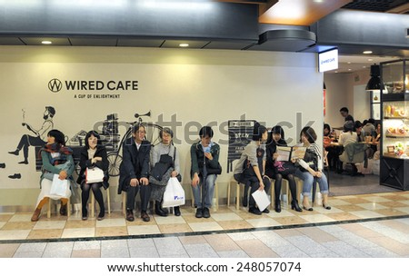 KYOTO, JAPAN-NOVEMBER 9, 2014; People sitting and waiting in line to enter a cafe in the shopping center of the Central Station building.November 9, 2014 Kyoto, Japan - stock photo