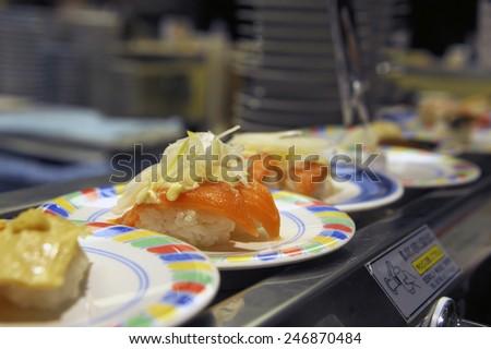 Kyoto, Japan-November 5, 2014; salmon sushi at a conveyor belt at a cheap sushi restaurant. Selective focus at the salmon sushi.November 5, 2014 Kyoto, Japan - stock photo