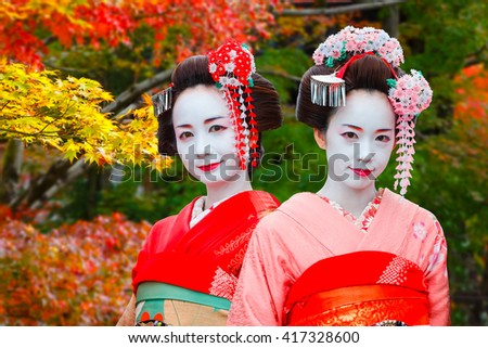 """KYOTO, JAPAN - NOVEMBER 22 2015: Unidentified """"Maiko"""" girls or apprentice Geisha are in a Japanese garden in autumn - stock photo"""