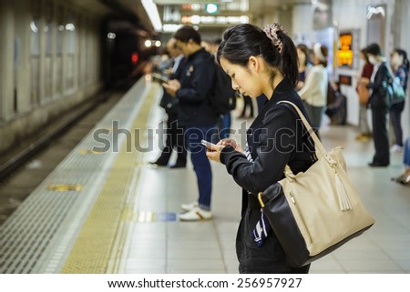 KYOTO, JAPAN - OCTOBER 23: People on a platform in Kyoto, Japan on October 23, 2014. Unidentified Japanese female uses her device while waits for a train on a plateform