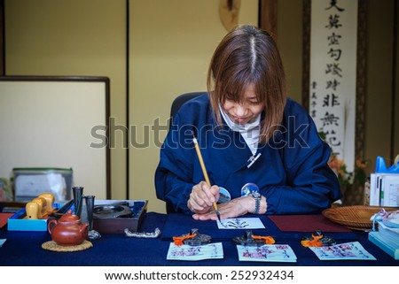 KYOTO, JAPAN - OCTOBER 21: Religious Volunteer in Kyoto, Japan on October 21, 2014. Unidentified Religious Volunteer writes calligraphy on a paper for using as a talisman in Ssisho-in temple