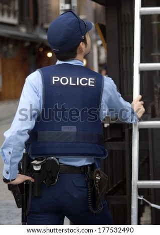 KYOTO, JAPAN - SEPTEMBER 8: Japanese police officer investigates the scene of a crime on September 8, 2012, Kyoto, Japan. Crime is very rare in Japan, it is one of the safest country in the world.