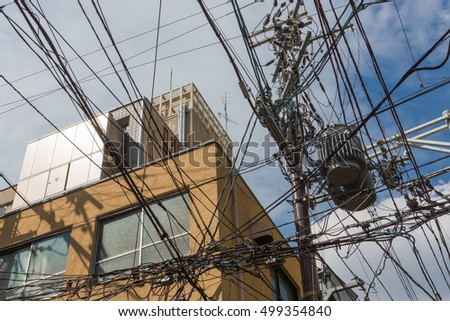 Kyoto, Japan - September 16, 2016: Power and communication cables create multiple cable nests as they are tangled under and above each other above the streets of Kyoto.