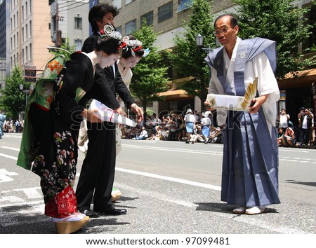 KYOTO - JULY 17: Two geishas bow to thank a participant of the famous annual Gion Festival held on July 17 2010 in Kyoto, Japan. Geishas often participate on traditional celebrations. - stock photo