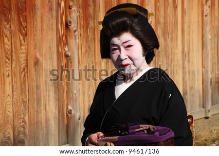 KYOTO - NOV 21: Unidentified old geisha outdoors on November 21 2009 in Gion district, Kyoto, Japan. Geishas are skilled in traditional arts such as music, dance, singing and tea ceremony. - stock photo
